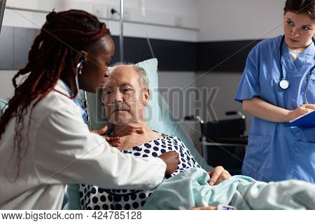 African American Cardiologist Checking Examining Senior Patient Heart, Using Stethoscope While Patie