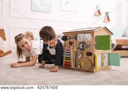Little Boy And Girl Playing With Busy Board House On Floor In Room