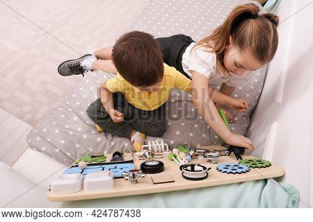 Little Boy And Girl Playing With Busy Board On Bed In Room, Above View