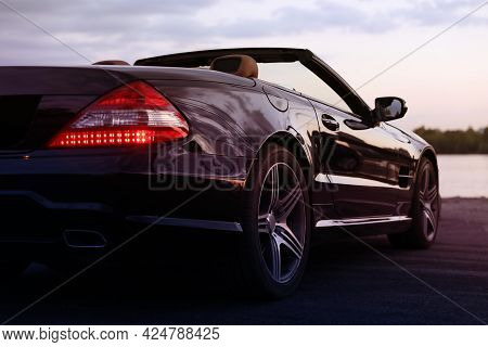 Luxury Black Convertible Car Outdoors In Evening