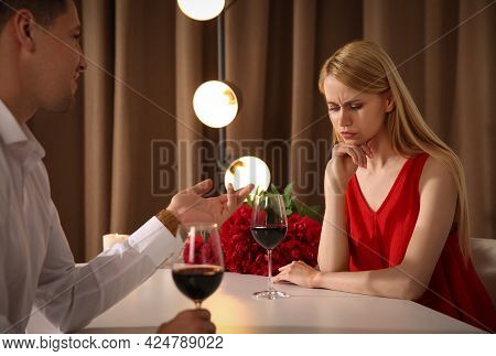 Displeased Young Woman And Overtalkative Man In Restaurant. Failed First Date