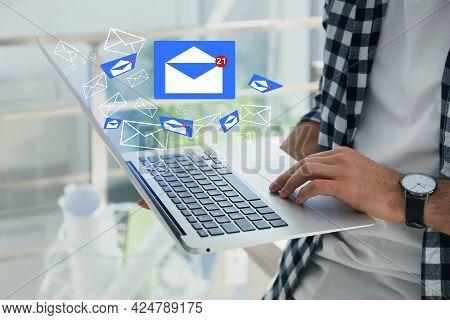 Man Sending Emails Via Laptop At Home, Closeup