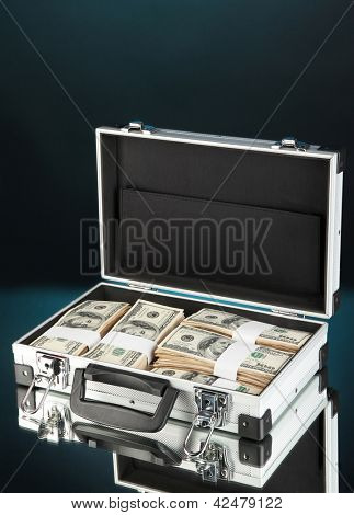 Suitcase with 100 dollar bills on dark color background