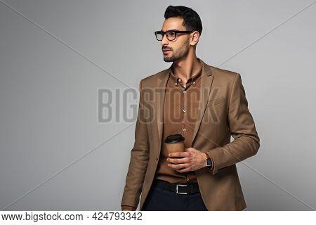 Bearded Arabian Businessman Holding Takeaway Drink Isolated On Grey