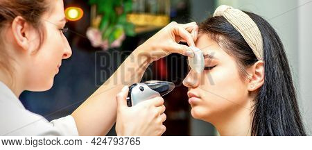 Side View Of A Make-up Artist Using Aerograph Making An Airbrush Makeup Foundation On A Female Face