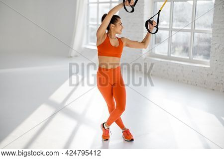 Athletic Woman In Bright Sportswear Stretching On Suspension Straps At White Gym. Trx Training On Fi