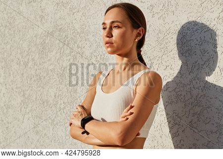 Side View Portrait Of Slim Attractive Woman Wearing White Top Standing With Confident Facial Express