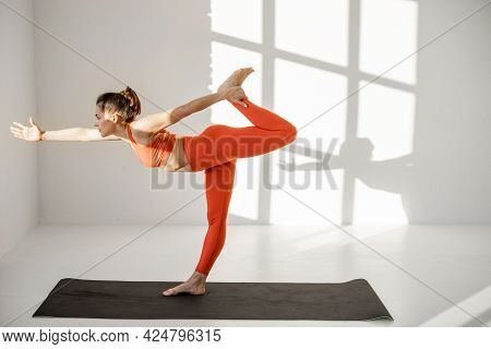 Athletic Woman In Bright Sportsclothes Holding Yoga Pose, Practising Hatha Yoga At White Room Alone