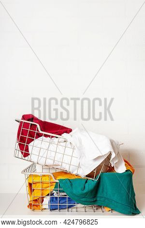 Huge Stack Of Colorful Clothes In Baskets In Laundry Room. Improper Storage Of Things, Mess, Disorde