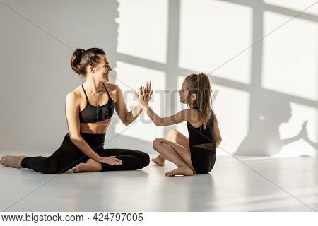 Young Athletic Mom Or Sports Trainer Giving A Five To A Little Girl During Sports Activities Indoors