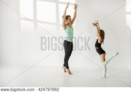 Young Mom Or Sports Coach Trains Little Girl In Rhythmic Gymnastics At White Sunny Sport Classroom.