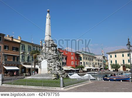 City Center Of The Town Called A Lazise On The Shores Of Lake Garda With A Monument Obelisk To Remem