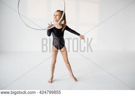 Little Girl Practising Rhythmic Gymnastic With A Ring At White Room. Childrens Gymnastics And Traini