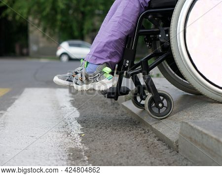 A Paralyzed Girl In A Wheelchair Prepares To Run Over The Border In Front Of A Pedestrian Crossing.