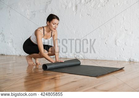 Young slim brunette fitness woman getting ready for stretching exercise on a sports mat in the studio