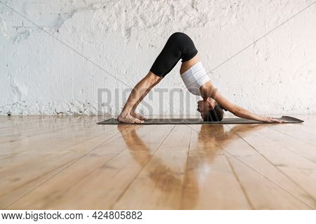 Young slim brunette fitness woman stretching on a sports mat in the studio side