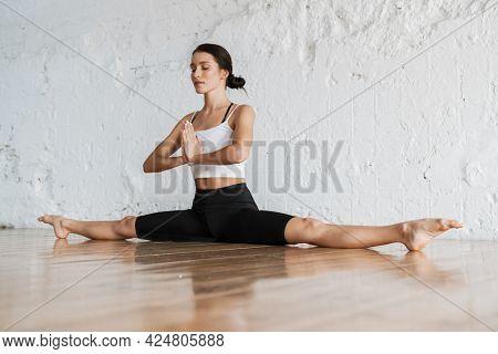 Calm young brunette white woman on sportswear sitting in split on a floor of a studio eyes shut