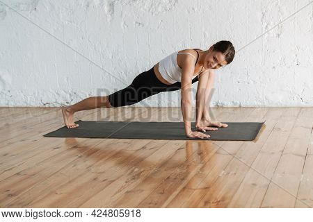 Young smiling slim brunette fitness woman stretching on a sports mat in the studio side