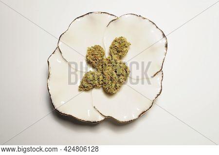 Marijuana Buds In White Ceramic Dish, Flat Lat, Top View. Cannabis Flowers On White Background. Hemp