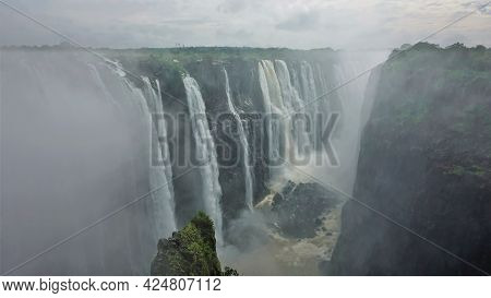 Unique Victoria Falls. Streams Of Water Rush Down From The Edge Of The Gorge. At The Bottom There Is