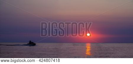 Sunset Over Ocean With Jetski. Silhouette Of A Man On A Jet Ski In The Sun. Jetski At Sunset. Panora