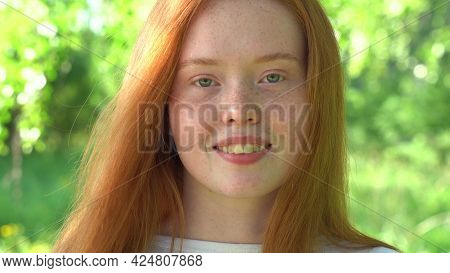 Portrait A Smiling Young Woman With Red Hair And Freckles Against The Backdrop Of A Bright Sunny Mea