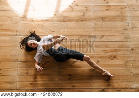 Young slim brunette fitness woman laying stretching on a sports mat in the studio top view