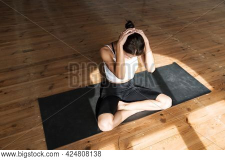 Young slim brunette fitness woman stretching on a sports mat in the studio
