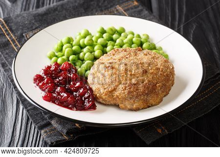 Delicious Veal Meatball With Green Peas Garnish And Lingonberry Jam Close-up In A Plate On The Table