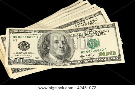 Stack of one hundred dollars banknotes close-up isolated on black