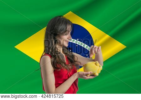 Economy In Brazil. Accumulating And Saving Money In Brazil. Woman Putting Money Coin In Piggy Bank F