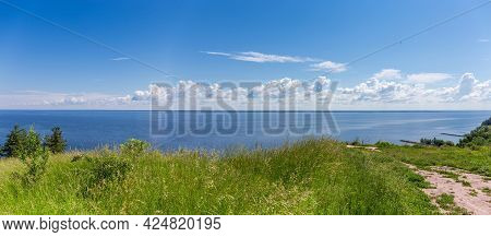 Panoramic View Of Big Reservoir From Steep Shore With Tall Grass On A Foreground Against The Sky Wit