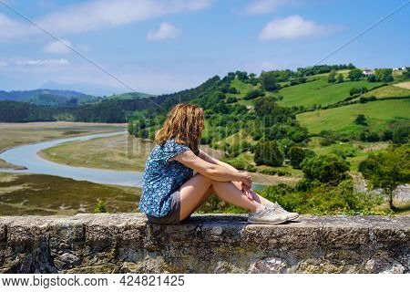 Woman Sitting On A Stone Wall And Contemplating The Green Landscape.