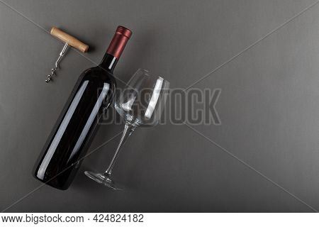 Corked Red Wine Bottle, Corkscrew And Empty Wine Glass On Gray Background. Alcoholic Drink. Winemaki