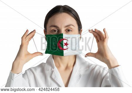 Respirator With Flag Of Algeria Doctor Puts On Medical Face Mask Isolated On White Background.