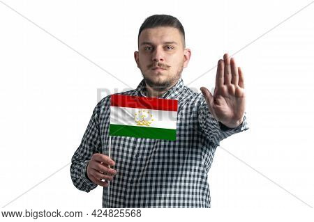 White Guy Holding A Flag Of Tajikistan And With A Serious Face Shows A Hand Stop Sign Isolated On A