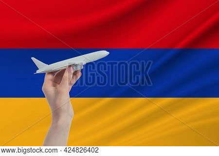 Airplane In Hand With National Flag Of Armenia. Travel To Armenia.