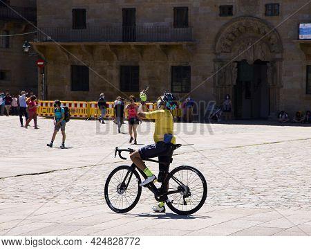 Santiago De Compostela (spain), June 25, 2021. A Pilgrim On A Bicycle Takes A Photo. Tourists And Pi