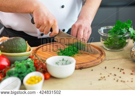 Young chef is cutting herbs and parsley in a modern kitchen. The man prepares food at home. Cooking healthy and tasty food.