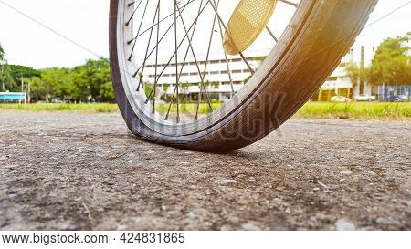 An Old Vintage Style Bicycle That Has Its Back Flat Tire Parking At The Parking Area In The Evening