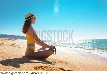Meditation By The Sea On A Sunny Day. Young Caucasian Woman In A Yellow Swimsuit Sits On The Golden