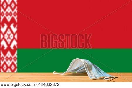 A Medical Mask Lies On The Table Against The Background Of The Flag Of Belarus. The Concept Of A Man