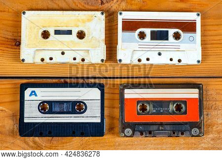 Four Old Audio Cassettes On A Wooden Planks Background Closeup
