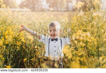 Little Boy Having Fun And Waves His Hands To The Camera In Nature In The Summer. Cute Adorable Child
