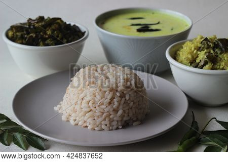 Vegetarian Meals Prepared In Kerala Style. The Serving Includes Boiled Red Rice, Stir Fried Onions W