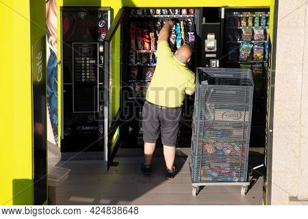 Galicia, Spain; June 25, 2021: Rear View Of A Worker Replenishing A Vending Machine