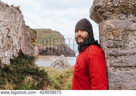 Portrait Of Rude Man, With Beard And Piercings, Looking At Camera Leaning On Stone Ruins Near The Se