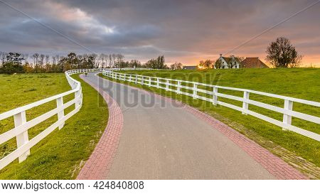 Dutch Countryside Landscape With Historical Houses In Evening Along A Curved Road With White Fence I