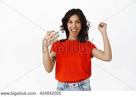 Yes I Did It. Smiling Young Woman Rejoice With Smartphone, Winning Mobile Video Game, Achieve Goal I