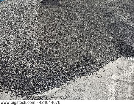 A Pile Of Granite Gravel On The Dock Ready To Be Loaded Onto The Ship. Bulk Cargo In A Heap At The B